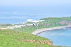 Witte quadrocopter die die over het overzees vliegen, manueel ondanks de wind in werking wordt gesteld stock foto