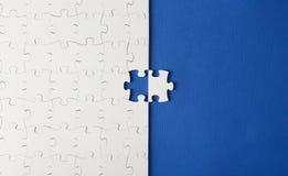 Witte raadsels op een blauwe achtergrond met één ontbrekend stuk royalty-vrije stock foto's