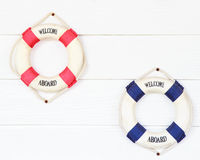 Witte Reddingsboei met onthaal aan boord op witte muur Stock Fotografie