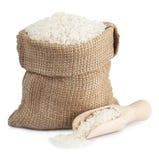 Witte rijst in een zak en een houten die lepel op witte backgro wordt geïsoleerd Stock Afbeeldingen