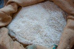 Witte rijst in jute in het pakhuis stock foto's