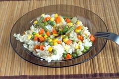 Witte rijst met groenten op plaat over rieten mat Royalty-vrije Stock Fotografie