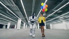 Witte robotgangen met een vrouw, die haar hand houden stock footage