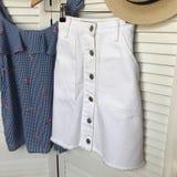Witte rok met een blauwe blouse op de achtergrond van een witte scre stock fotografie