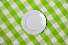 Witte ronde plaat op groen gecontroleerd tafelkleed Royalty-vrije Stock Foto