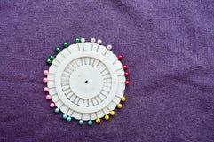 Witte, ronde speld, naaldbed met gekleurde naalden stock fotografie