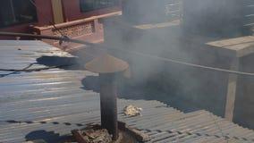 Witte rook van een ijzerpijp op het dak