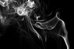 Witte rookwervelingen op een zwarte achtergrond stock afbeelding