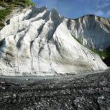 Witte rotsen en het zwarte zand Iturup, het Russische Kurils-Eiland Stock Afbeeldingen