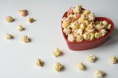 Witte roze popcorn in de kom van de hartvorm stock afbeeldingen