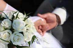 Witte rozen en handen. Stock Afbeeldingen