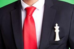 Witte schaakkoning in zak van een zakenman Stock Afbeeldingen
