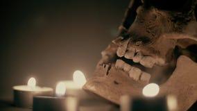 Witte schedel in de cirkel van kaarsen, op een rokerige mistige achtergrond, Halloween-thema Kaarslichttrillingen, knipoogje, het stock video