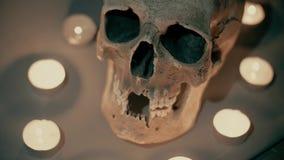 Witte schedel in de cirkel van kaarsen, op een rokerige mistige achtergrond, Halloween-thema Kaarslichttrillingen, knipoogje, het stock footage