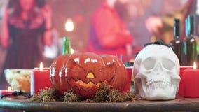 Witte schedel en een pompoen kwaad hoofd op een houten lijst met een Halloween-partij op de achtergrond stock videobeelden