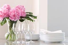 Witte schotels, wijnglazen & pioenen Stock Afbeelding
