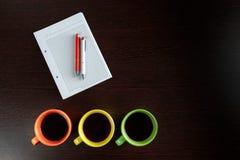Witte sketchbook die op een donkere bruine houten lijst met liggen oranje en witte pennen naast de koppen van koffie Stock Foto's