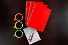 Witte sketchbook en oranje notitieboekjes die op een donkere bruine houten lijst met liggen oranje en witte pennen naast de koppe Royalty-vrije Stock Afbeeldingen