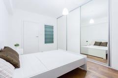 Witte slaapkamer in eigentijdse flat stock foto