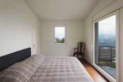 Witte slaapkamer, grote vensters stock afbeelding
