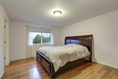 Witte slaapkamer met donker bevlekt houten bed met lagere laden Royalty-vrije Stock Fotografie