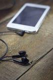 Witte slimme telefoon met oortelefoons Stock Fotografie