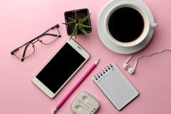 Witte smartphone en een kop koffie en bureaulevering op een heldere roze achtergrond Mening van hierboven royalty-vrije stock fotografie