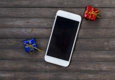 Witte smartphone met blauwe en rode giften Gadget op rustieke houten lijst Royalty-vrije Stock Foto