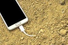 Witte smartphone met een lader die in het zand wordt gestopt voor en achter vage achtergrond stock foto
