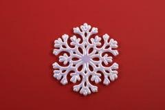 Witte Sneeuwvlok op Rood Stock Afbeeldingen