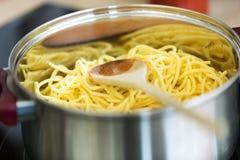 Witte spaghetti op braadpan in de keuken thuis stock foto
