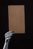 Witte spookhand met zwarte spijkers die leeg karton houden Stock Foto