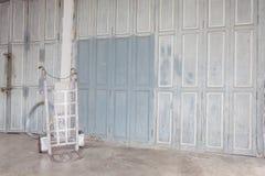 Witte staalkruiwagen dichtbij vuile oude muur Royalty-vrije Stock Foto's