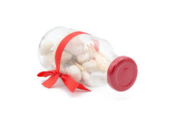Witte stenen in verfraaide glasfles en rode boog Royalty-vrije Stock Foto's