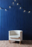 Witte stoffenleunstoel op een achtergrond van blauwe muur met retro slinger van gloeilampen Textuur voor het ontwerp Stock Foto's