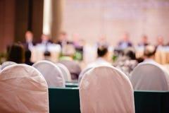 Witte stoffenstoel met onscherp van auditorium voor aandeelhouders die 'samenkomen stock fotografie