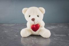Witte stuk speelgoed teddybeer met hart op een grijze achtergrond Het symbool van de dag van minnaars De dag van de valentijnskaa Stock Foto's