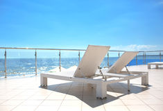 Witte sunbeds bij het terras van een hotel dichtbij het tropische strand Heel wat witte ligstoelen dichtbij het overzeese strand  Stock Fotografie
