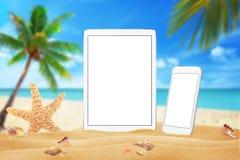 Witte tablet en slimme telefoon met het geïsoleerde witte scherm voor model De zomer op strand, overzees, zand, blauwe hemel, pal stock afbeelding