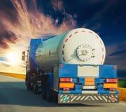 Witte tanker en vrachtwagens die langs de asfaltweg rond het gele bloeiende raapzaadgebied drijven in platteland stock foto