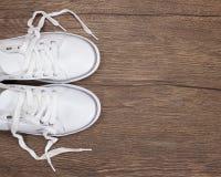 Witte tennisschoenen op donkere houten oppervlakte Royalty-vrije Stock Afbeeldingen