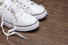 Witte tennisschoenen op donkere houten oppervlakte Royalty-vrije Stock Foto's