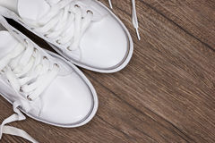 Witte tennisschoenen op donkere houten oppervlakte Stock Fotografie