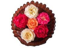 Witte thee, oranje en rode rozen die in een glas drijven Stock Fotografie