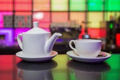 Witte theepot en theekop op de achtergrond van kleurenlichten Royalty-vrije Stock Foto