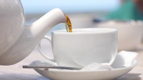 Witte theepot gietende thee in kop in langzame motie in strandkoffie door het overzees met zonlicht 3840x2160 stock video