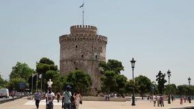 Witte toren en mensen op de waterkant in Thessaloniki, Griekenland stock footage