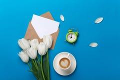 Witte tulpen met bloemblaadjes, kop van koffie, een liefdenota en een envelop op een blauwe achtergrond stock afbeeldingen