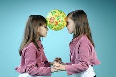 Witte tweelingzusters die pret met bal hebben Royalty-vrije Stock Foto