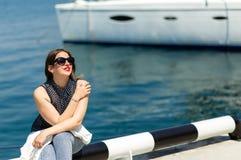In witte uitrusting van mooie lachende vrouw in zonnebril die op de witte jachtachtergrond stellen royalty-vrije stock afbeelding